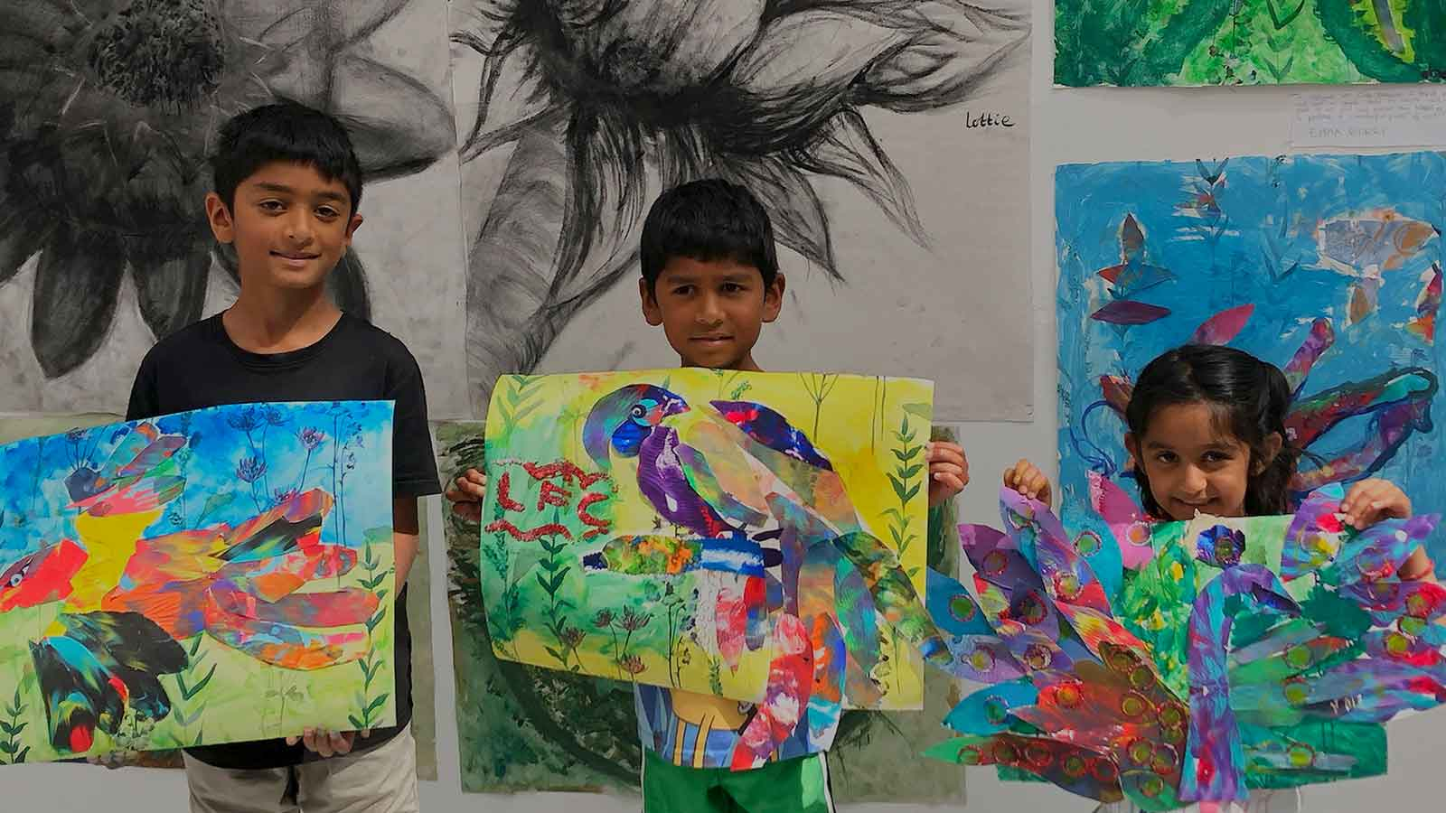 Children proudly displaying their artworks from Topical Tuesday with Art at the Heart CIC's Art Club