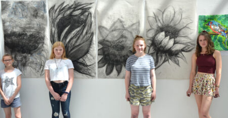 Art Lab standing next to big charcoal drawings in the gallery