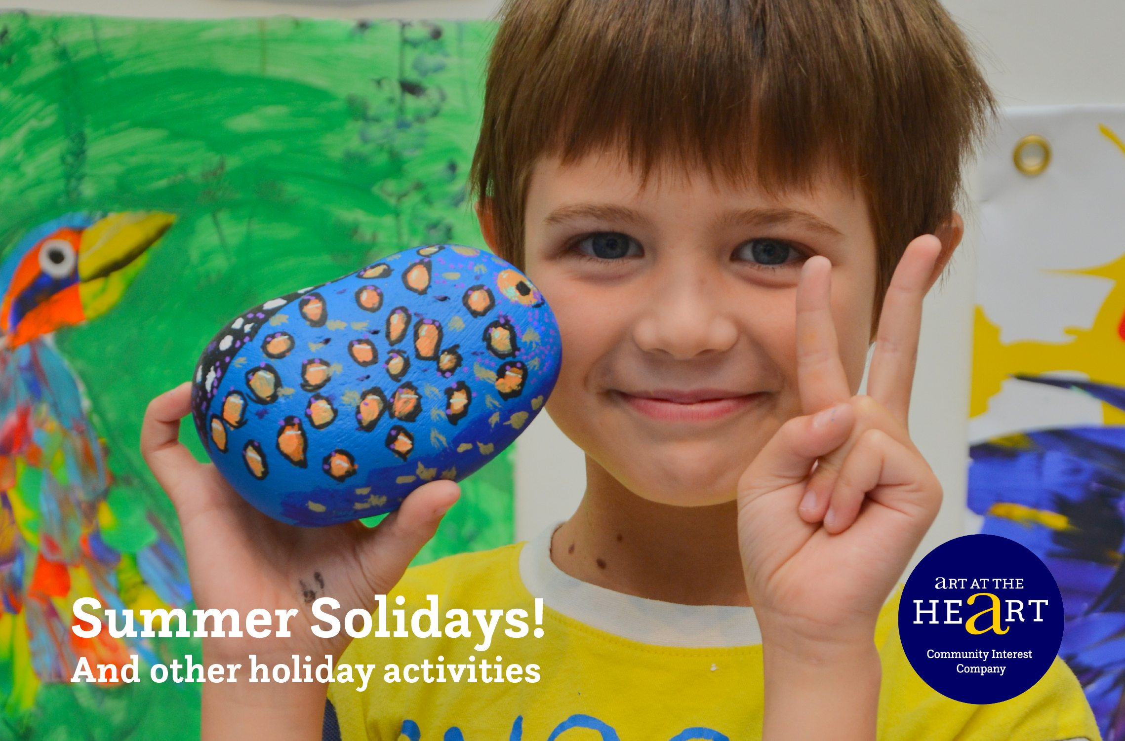 Photo of a boy holding a painted rock, advertising Art at the Heart's holiday programme