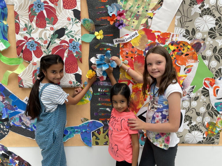 Three girls standing by origami flowers on the jungle mural