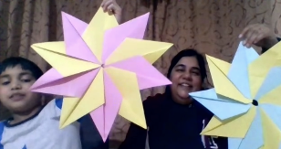 A mother and child holding up pink, yellow and blue origami flowers