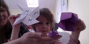 A boy holding up his origami creations